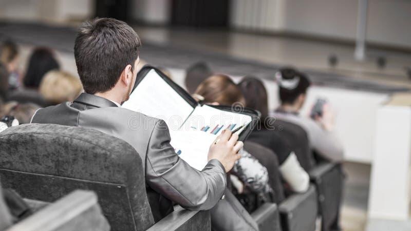 Succesvolle zakenman die met financi?le documenten in een conferentieruimte zitten voor bedrijfspresentaties stock afbeelding