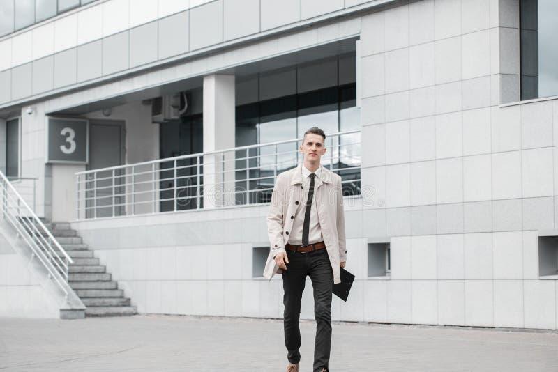 Succesvolle zakenman die onderaan de straat lopen en in dag glimlachen stock afbeeldingen