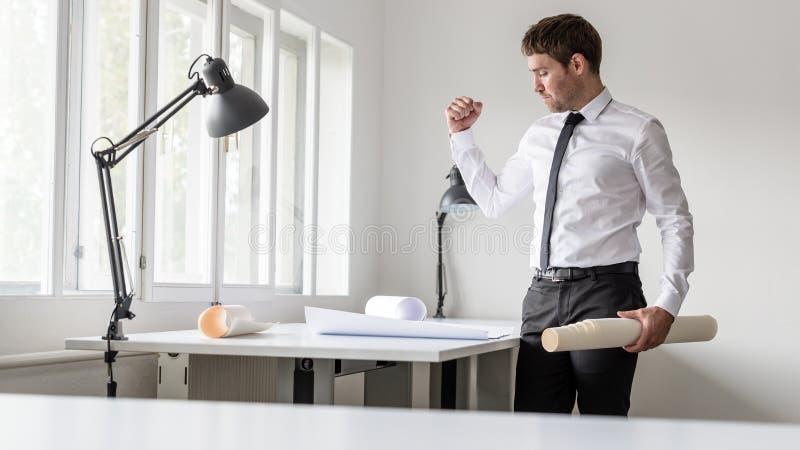 Succesvolle zakenman die zijn vuist opheffen terwijl het bekijken pla stock foto's