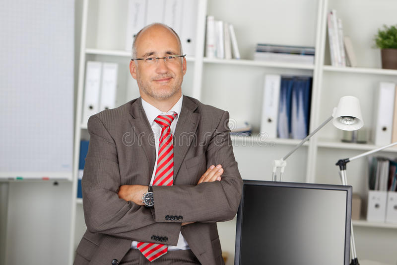 Succesvolle zakenman met gevouwen wapens royalty-vrije stock foto's