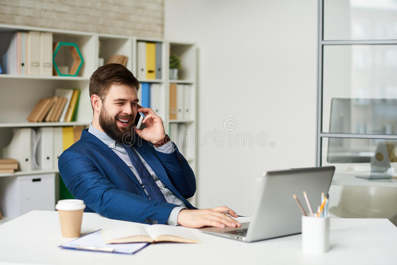 Succesvolle Zakenman Speaking telefonisch in Bureau stock foto's