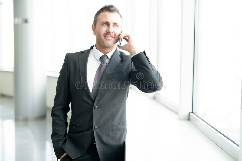 Succesvolle Zakenman Speaking telefonisch door Venster royalty-vrije stock foto