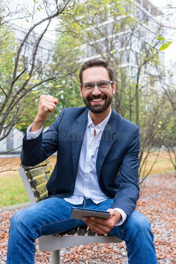 Succesvolle zakenmanzitting op bank in het park stock afbeelding