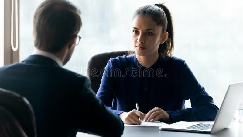 Succesvolle zakenvrouw praat met mannelijke collega tijdens briefing stock afbeelding