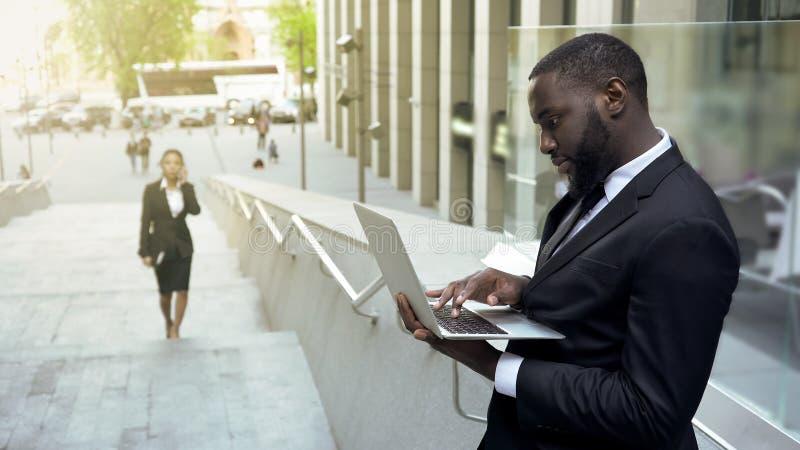 Succesvolle zwarte bedrijfsmens die in openlucht aan laptop werken die, voor vergadering voorbereidingen treffen stock afbeeldingen