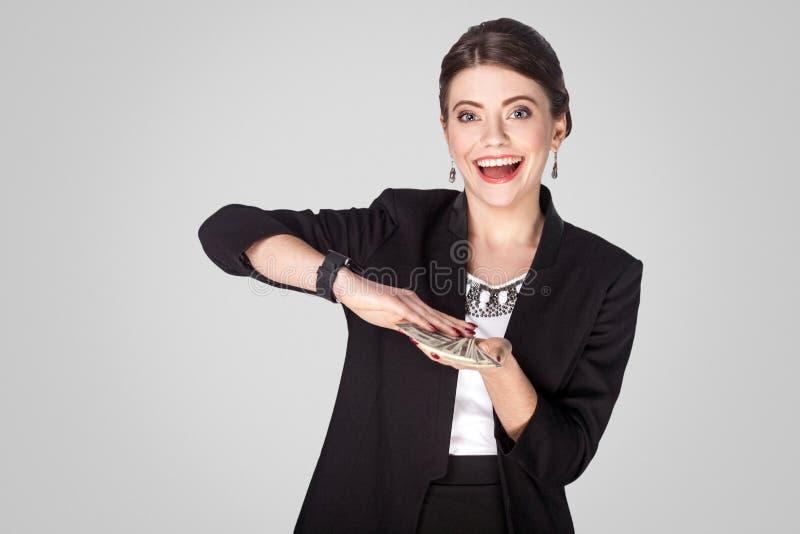 Succesvrouw die bij contant geld, dollar en toothy glimlach tonen Studio s stock fotografie
