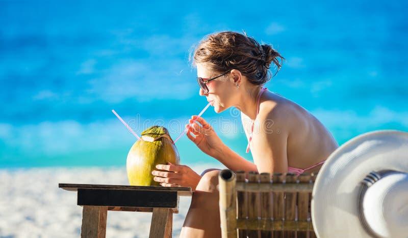 Succo bevente della noce di cocco della giovane donna mentre rilassandosi immagini stock