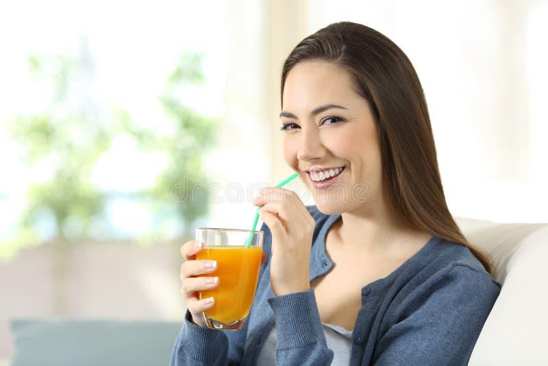 Succo d'arancia bevente della donna graziosa che esamina macchina fotografica fotografia stock