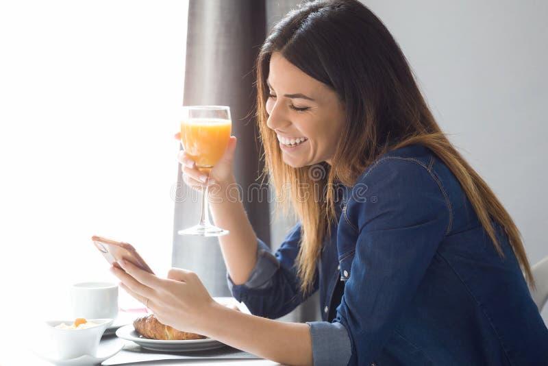 Succo d'arancia bevente della giovane donna graziosa mentre mandando un sms con il suo telefono cellulare nella sala da pranzo de fotografie stock