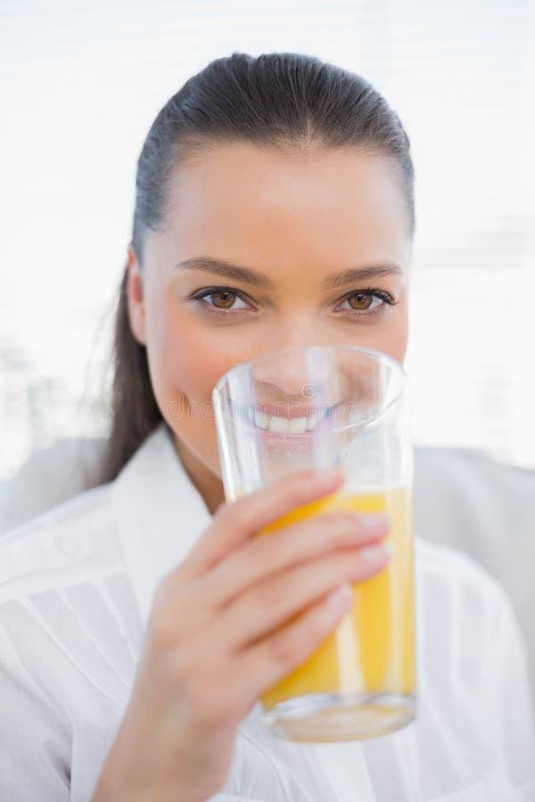 Succo d'arancia bevente sorridente della donna graziosa che si siede sullo strato accogliente immagini stock