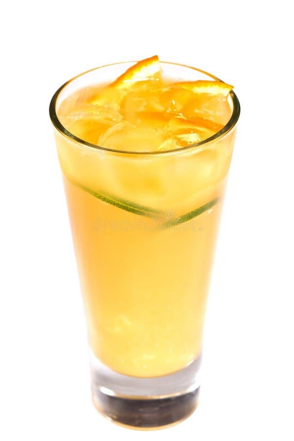 Succo d'arancia con i pezzi della frutta e del ghiaccio in un vetro su un fondo bianco isolato fotografia stock