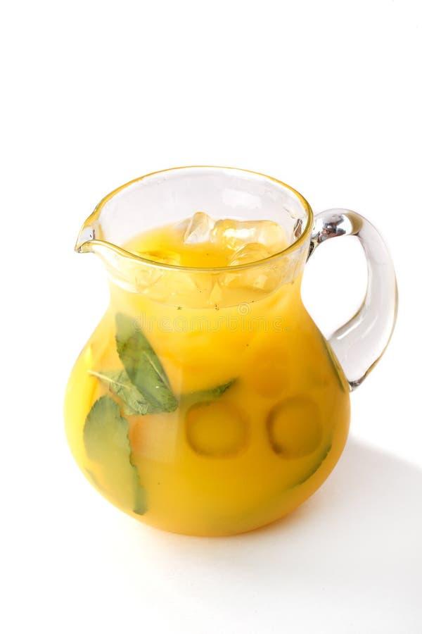 Succo d'arancia con i pezzi della frutta in una brocca su un fondo bianco isolato fotografia stock