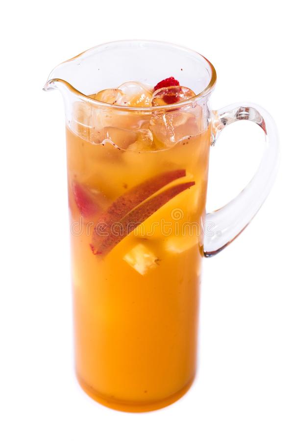 Succo d'arancia con i pezzi della frutta in una brocca su un fondo bianco isolato fotografie stock libere da diritti