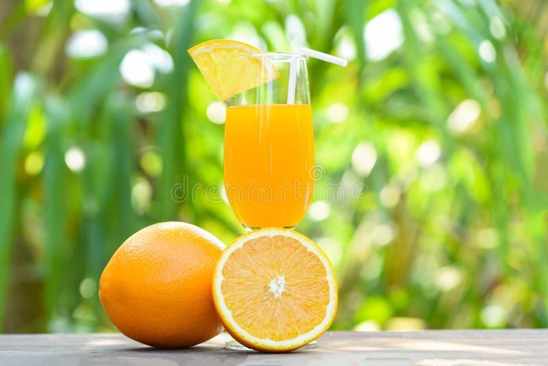 Succo d'arancia con la frutta arancio del pezzo su vetro con il fondo di estate di verde della natura immagini stock libere da diritti