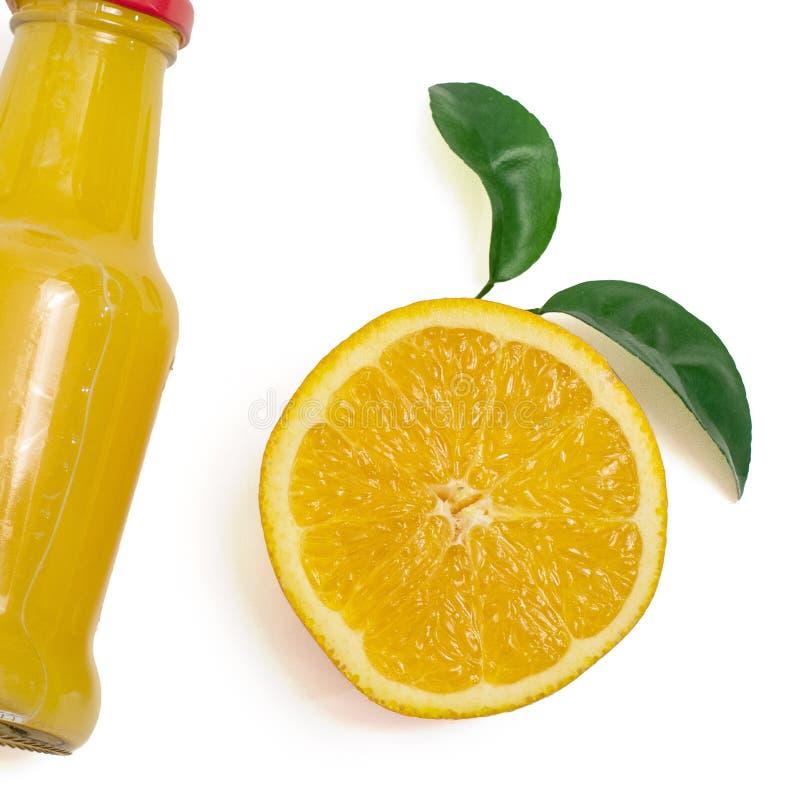 Succo d'arancia delizioso in una bottiglia ed in una fetta di arancia accanto  Isolato su bianco Vista superiore fotografie stock