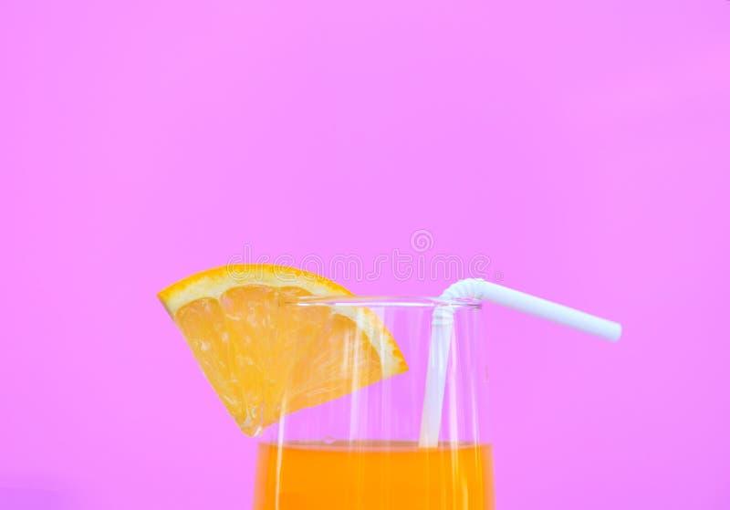 Succo d'arancia di estate con la frutta arancio del pezzo in vetro su fondo rosa fotografia stock libera da diritti
