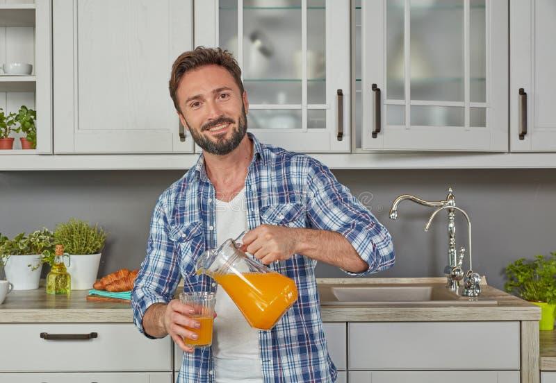 Succo d'arancia di versamento dell'uomo in buona salute immagini stock