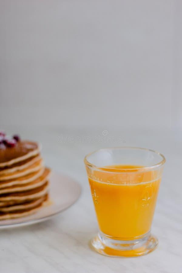 Succo d'arancia e pila di pancake sulla tavola di marmo fotografie stock libere da diritti