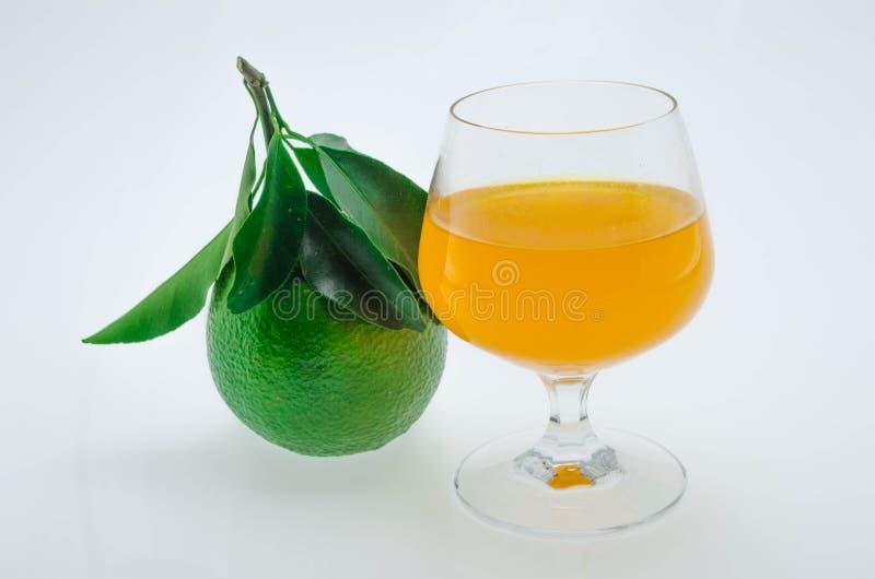 Succo d'arancia ed arance con le foglie su fondo bianco fotografia stock