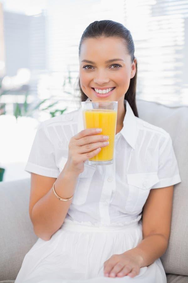 Succo d'arancia grazioso sorridente della tenuta della donna che si siede sullo strato accogliente fotografia stock libera da diritti