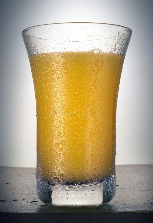 Succo d'arancia nelle gocce bagnate di vetro fotografia stock libera da diritti