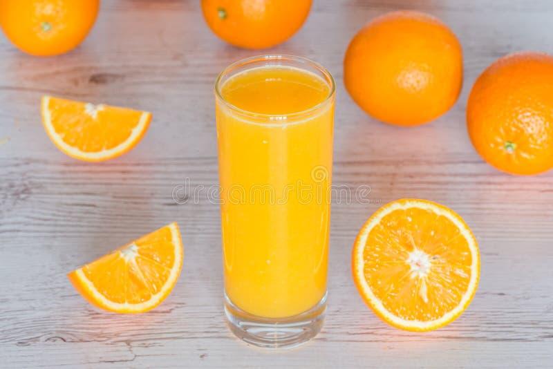 Succo d'arancia in vetro a fondo di legno leggero fotografia stock libera da diritti