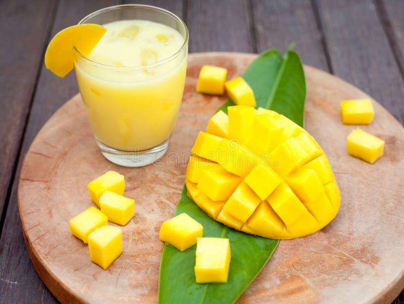 Succo del mango, frullato, frutta del mango su un fondo di legno fotografia stock