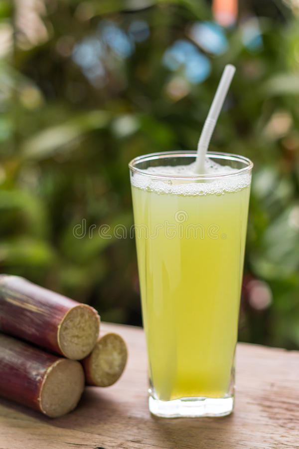 Succo della canna da zucchero con il pezzo di canna da zucchero su fondo di legno fotografia stock