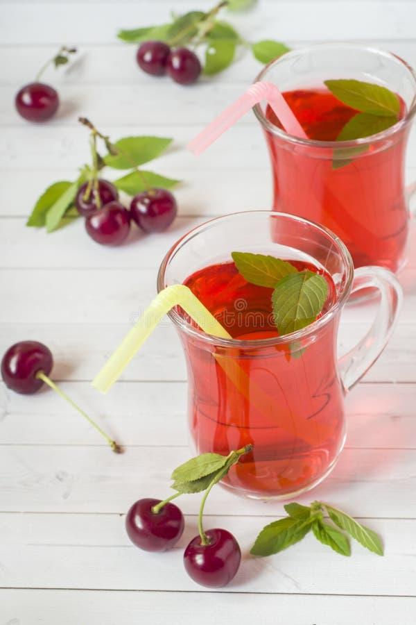 Succo della ciliegia con le foglie di menta e le ciliege fresche su una tavola di legno bianca fotografia stock libera da diritti