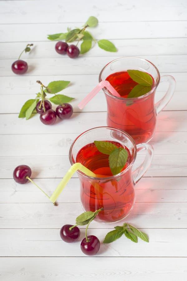 Succo della ciliegia con le foglie di menta e le ciliege fresche su una tavola di legno bianca fotografia stock