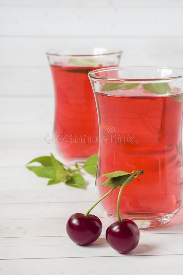 Succo della ciliegia con le foglie di menta e le ciliege fresche su una tavola di legno bianca fotografie stock libere da diritti