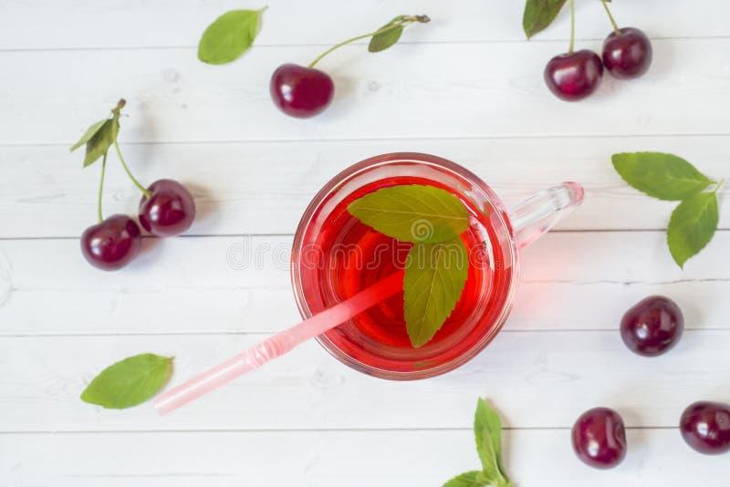 Succo della ciliegia con le foglie di menta e le ciliege fresche su una tavola di legno bianca immagine stock libera da diritti