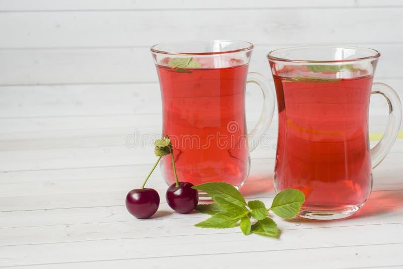 Succo della ciliegia con le foglie di menta e le ciliege fresche su una tavola di legno bianca Copi lo spazio fotografie stock