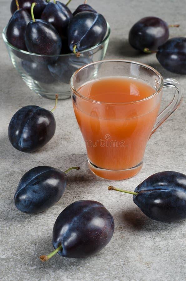 Succo della prugna in una tazza e nelle prugne blu su una tavola grigia fotografia stock libera da diritti