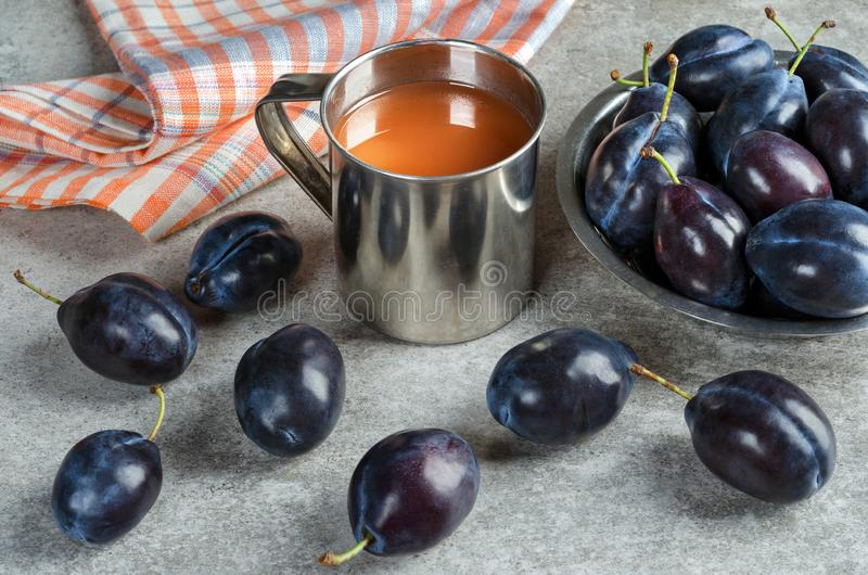 Succo della prugna in una tazza e nelle prugne mature fotografie stock