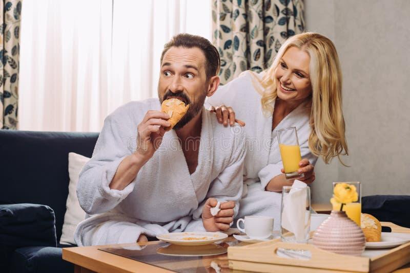 succo delle coppie mature felici e pasticceria beventi di cibo durante la prima colazione in hotel fotografia stock