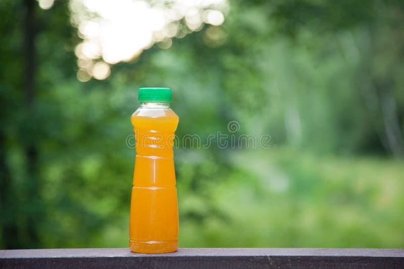 Succo di agrumi delizioso in una bottiglia di plastica sui precedenti della natura di estate fotografie stock libere da diritti
