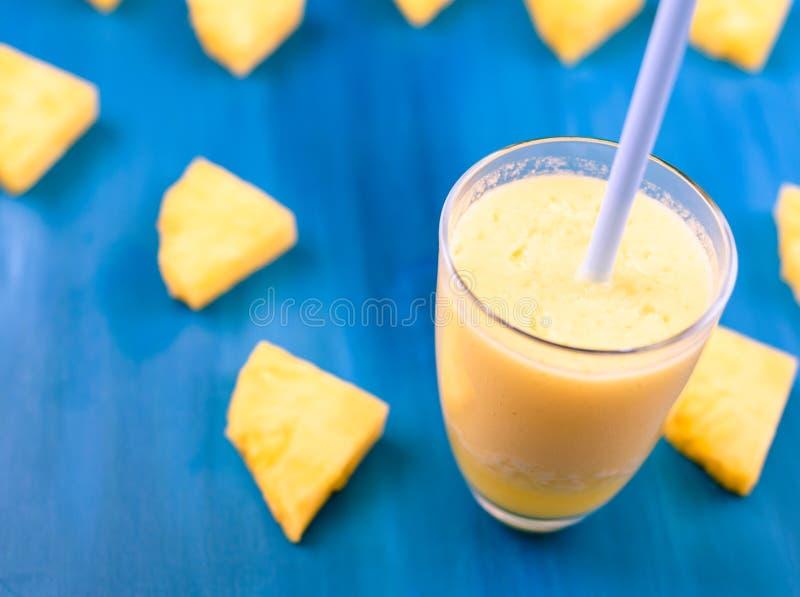Succo di ananas fresco nel vetro, fuoco selettivo sulla tavola blu di legno fotografia stock libera da diritti