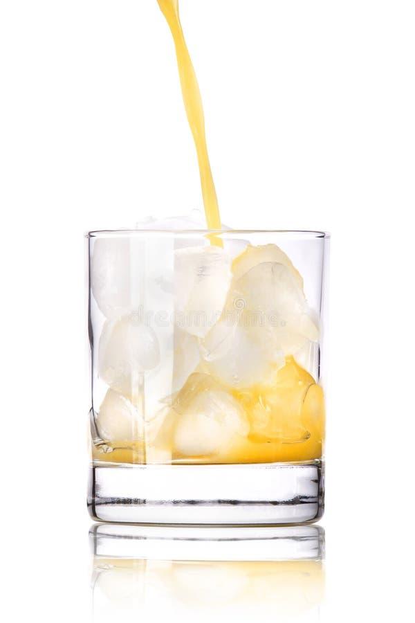 Succo di arancia fresco che versa dentro al vetro fotografia stock libera da diritti