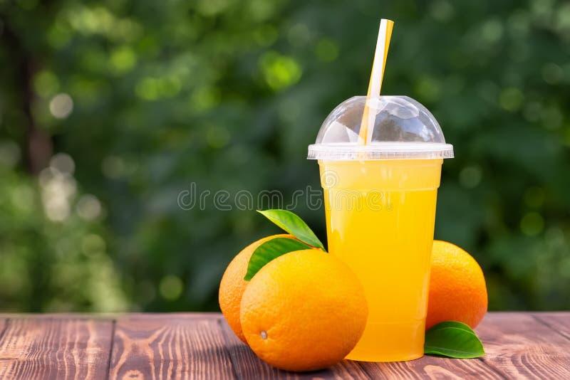 Succo di arancia in tazza di plastica immagini stock