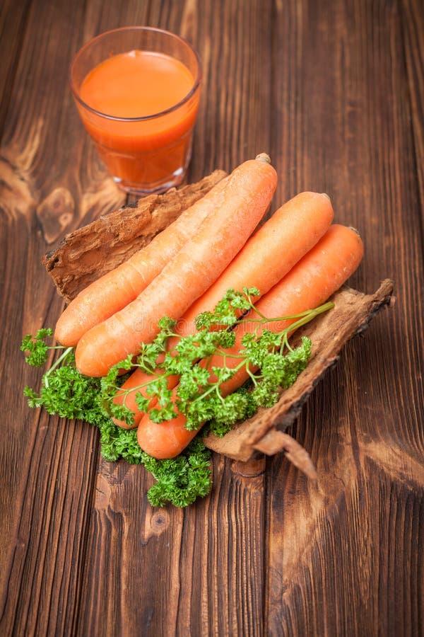 Succo di carota in bei vetri, verdure arancio del taglio e prezzemolo verde sul fondo di legno di marrone scuro Aranciata fresca  fotografia stock libera da diritti