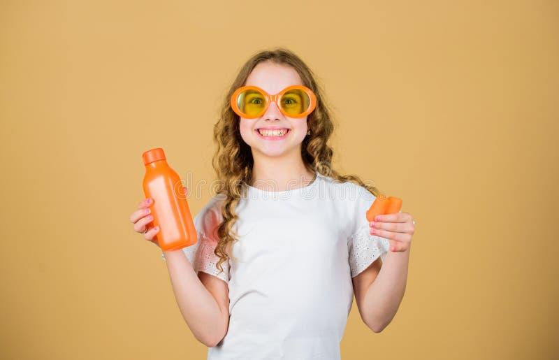 Succo di carota fresco della bevanda felice della ragazza Vacanza di estate bambina in vetri di modo Nutrizione della vitamina ri fotografie stock