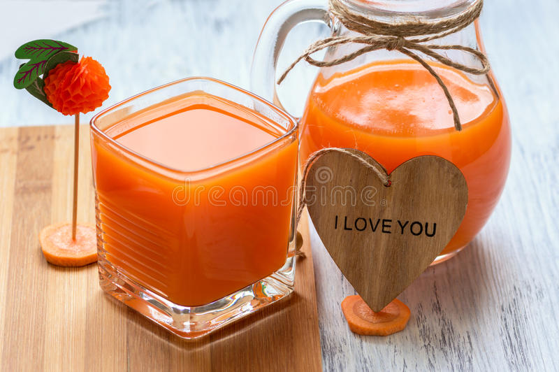 Succo di carota fresco in un vetro ed in una brocca fotografie stock libere da diritti