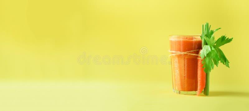 Succo di carota organico con le carote, sedano su fondo giallo Smothie della verdura fresca in vetro bandiera Copi lo spazio immagini stock