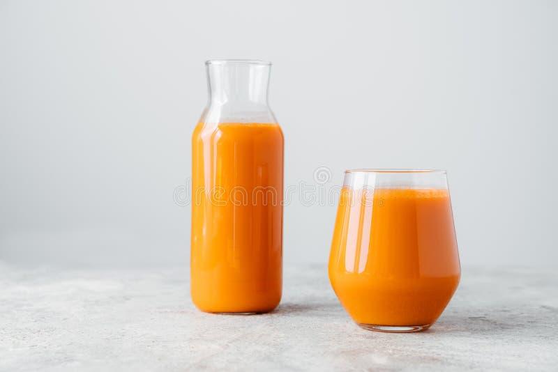 Succo di carota schiacciato fresco in bottiglia e vetro sulla tavola di legno isolata sopra fondo bianco Bevanda di verdure Bevan fotografie stock