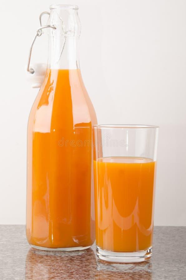 Succo di carota in un vetro ed in una bottiglia fotografie stock