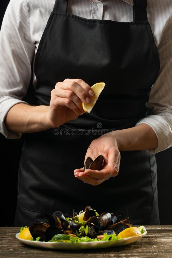 Succo di limone di versamento del cuoco unico con le cozze con l'insalata del vino bianco su un fondo scuro fotografia stock