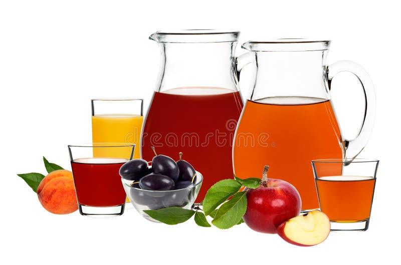 Succo di mela, della prugna e della pesca in vetri e decantatori fotografia stock