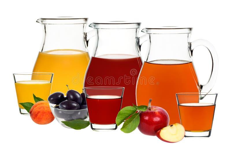 Succo di mela, della prugna e della pesca in vetri e decantatori fotografie stock libere da diritti