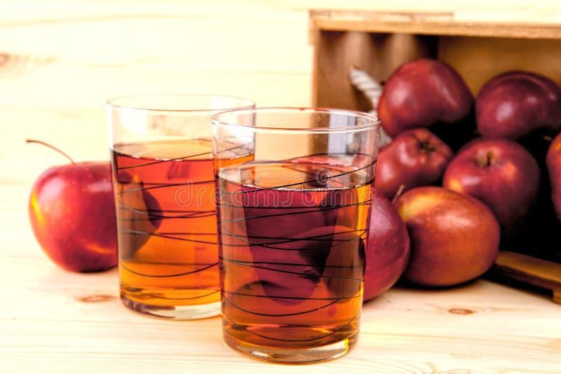 Succo di mele e mele fresche in una scatola di legno fotografie stock libere da diritti